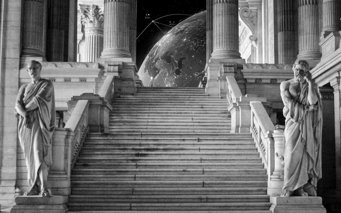 Two statues stand beside a stairwell inside the Palais de Justice. The earth stands at the top of the stairs.