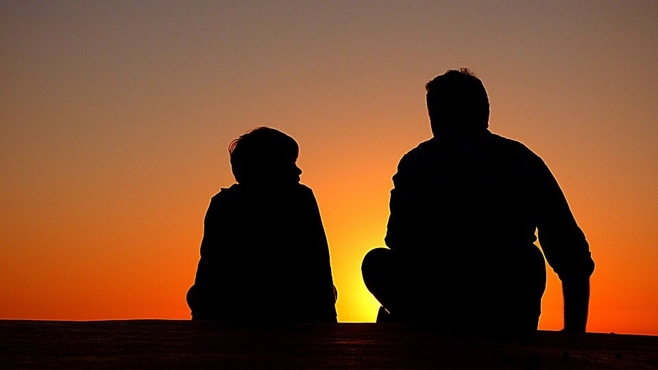 A silhouette of a man talking with his son while watching the sunset