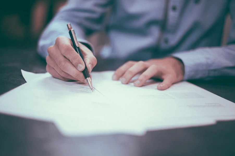 a hand of a man signing papers